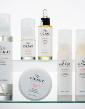 M Picaut Skincare produkter. Ekologiska produkter på glashylla. Samlingsbild för rengöringsmjölk, ansiktsvatten, ögonkräm, serum, hudkrämer och peelinmask.