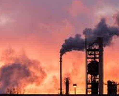 the image shows an oil factory with a sunset in the background.