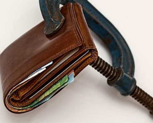 The picture shows a wallet crushed by a grip to represent italian financial crisis