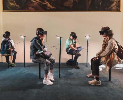 Tthe image highlights a group of people sitting on stools all wearing Hololens to communicate the development of virtual reality