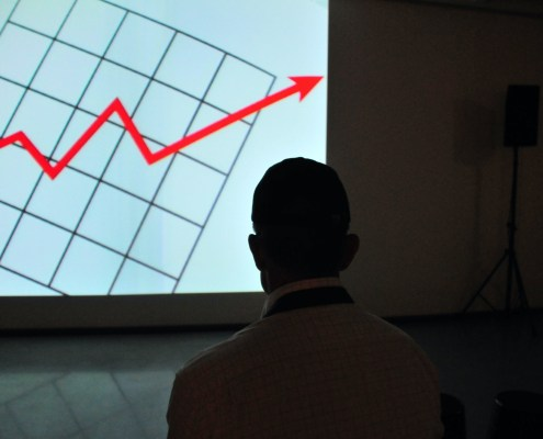 The image highlights a big red line chart and a person who is looking at it by frank-busch-PzifgmBsxCc-unsplash