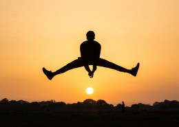 The image highlights a man jumping on a sunset