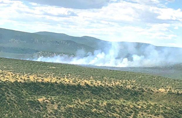 Light clouds of smoke rise from the Polles Fire the morning of July 6. The view is from the air and the smoke drifts to the right edge of frame.