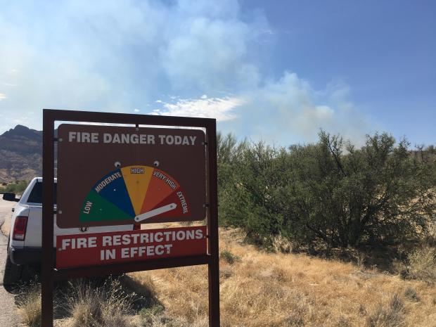 In the foreground is a Fire Danger Rating sign indicating EXTREME fire danger and fire restrictions. In the background is dense smoke issuing from the heel of the Telegraph Fire.