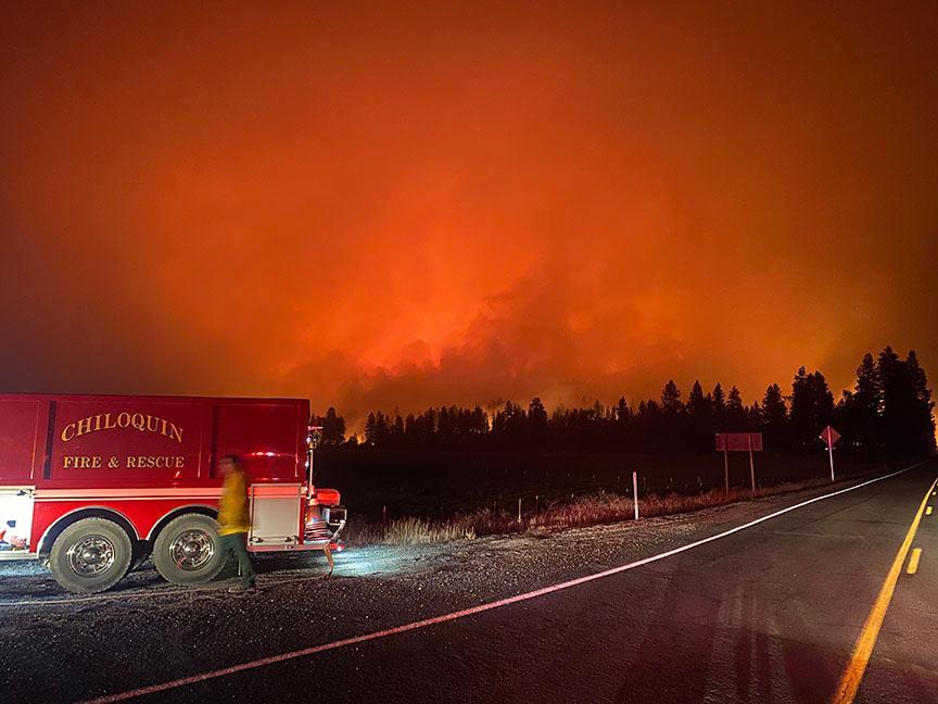 A Chiloquin Fire & Rescue truck is framed by the glow of fire in the near distance. A firefighter is also visible, walking alongside the truck.
