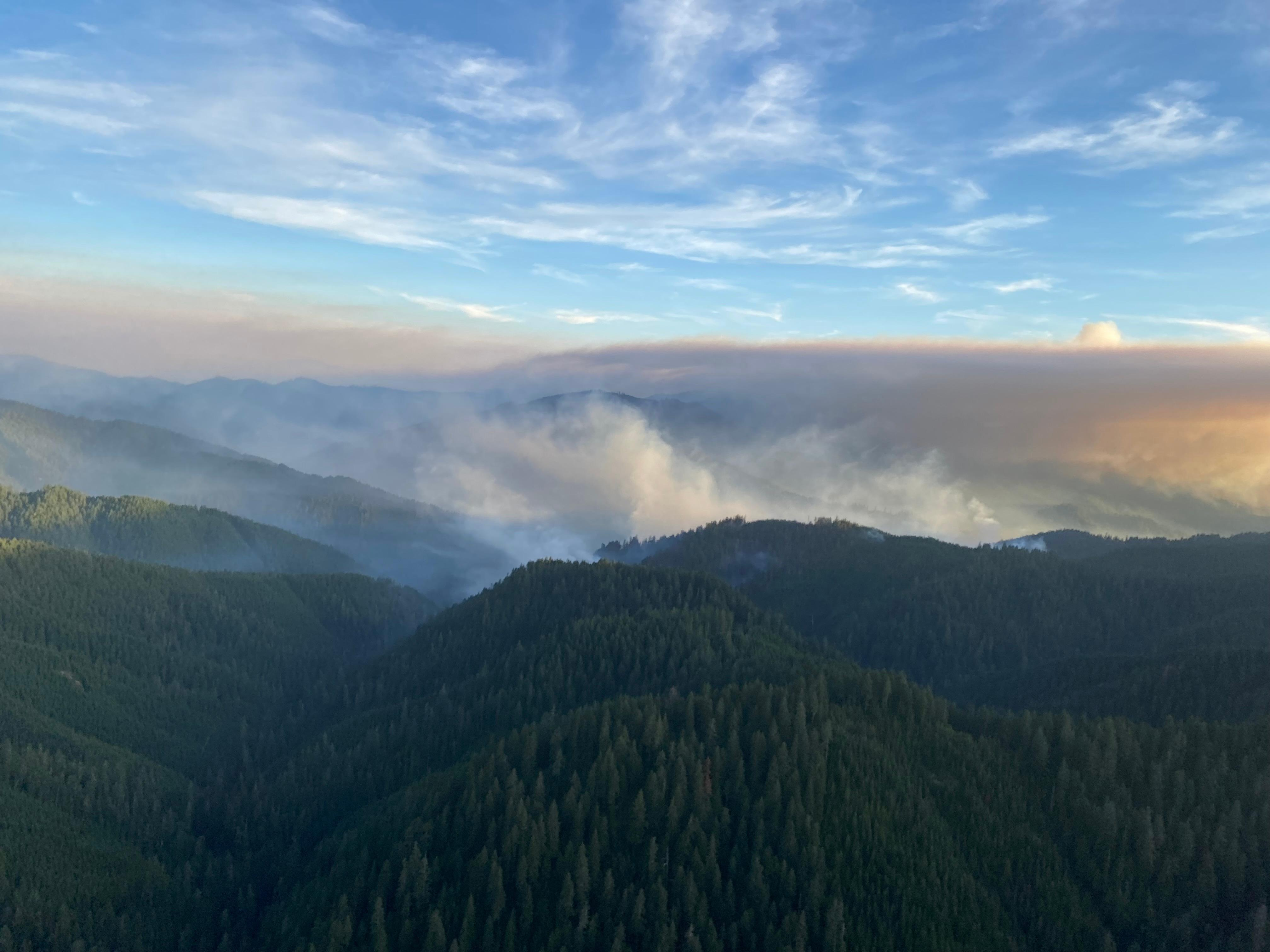 Blue sky visible above pink tinted smoke from forest fires. Below the smoke green forested mountains are visible.