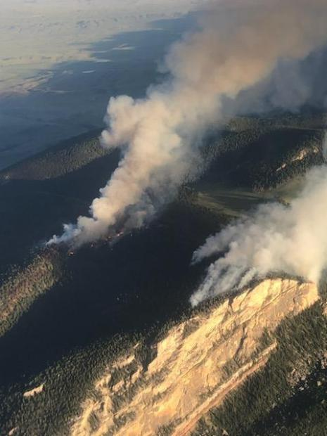 Two columns of smoke are rising from a forested area near a high vertical cliff.