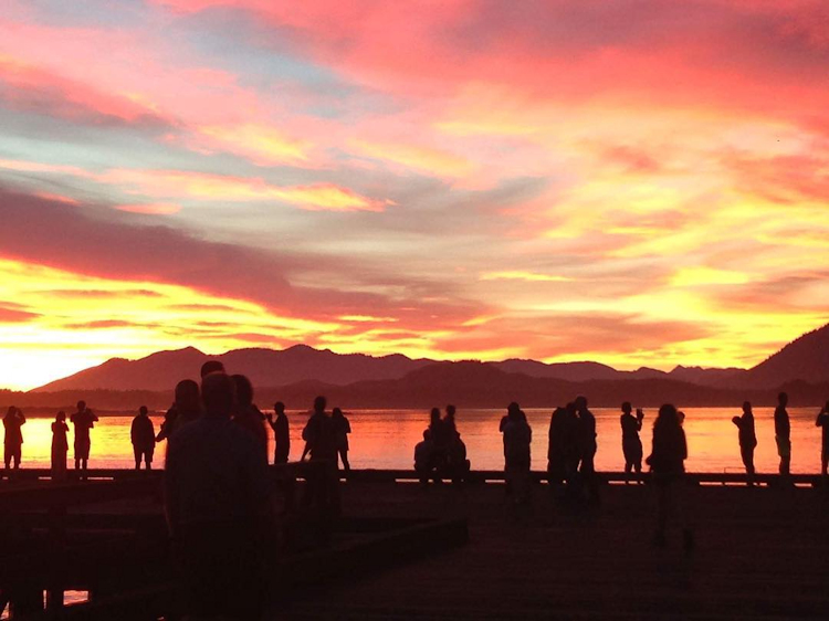 Beach goers view sunset.