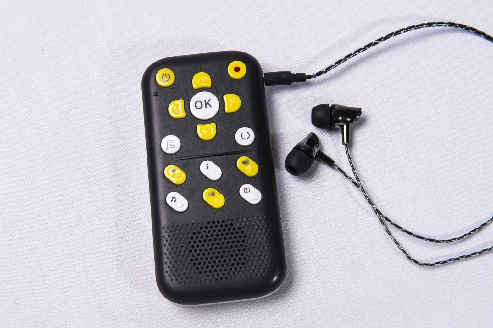 Foto de um leitor de livros digitais EVO E10 com um par de fones de ouvido conectados ao lado dele.