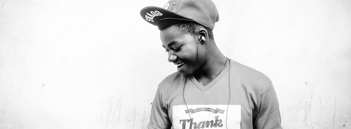 """Smiling male teen with brown skin wearing earbuds, a cap, and a t-shirt that says """"thank you."""""""