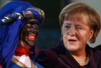 German Chancellor Merkel speaks with carol singer dressed as Balthasar at Chancellery in Berlin