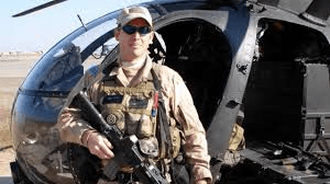 Gary A. Linfoot in uniform, with gun and helicopter