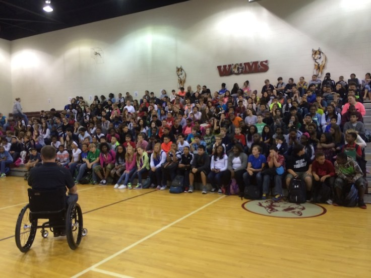 Gary Linfoot talking to student audience in gym alternate angle