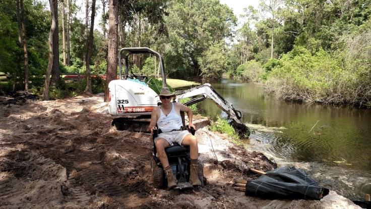 Kevin St. Amant in chair at work site beside river