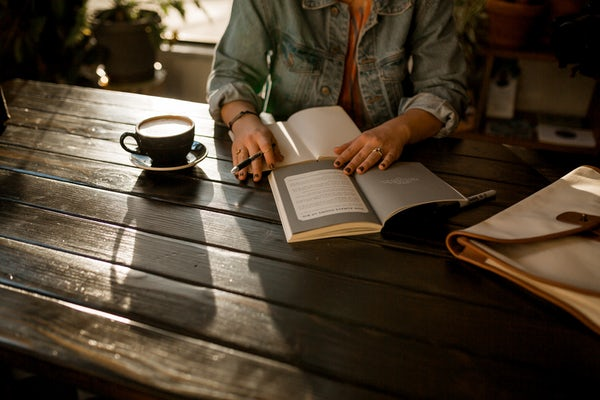 Picture of a woman reading and taking notes. This is associated to the IBR short story developmental edit.