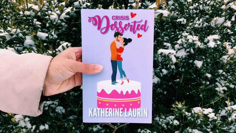 Independent Book review's Jaylynn Korrell holds the paperback of Crisis Desserted by Katherine Laurin in front of a snowy bush
