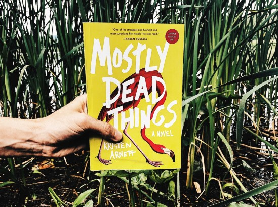 This is a paperback photo of MOSTLY DEAD THINGS by Kristen Arnett, held by Joe Walters of Independent Book Review in front of a swamp.