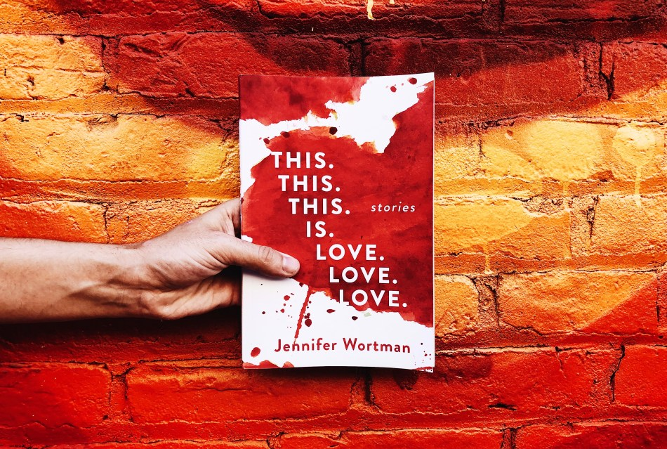 This is an Independent Book Review original photo of a hand holding the paperback book THIS. THIS. THIS. IS. LOVE. LOVE. LOVE.