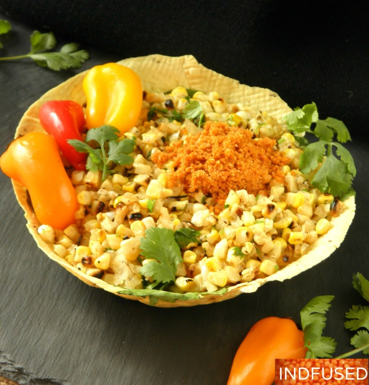 India's favorite street corn served hurda style with red chutney in an edible papad bowl!