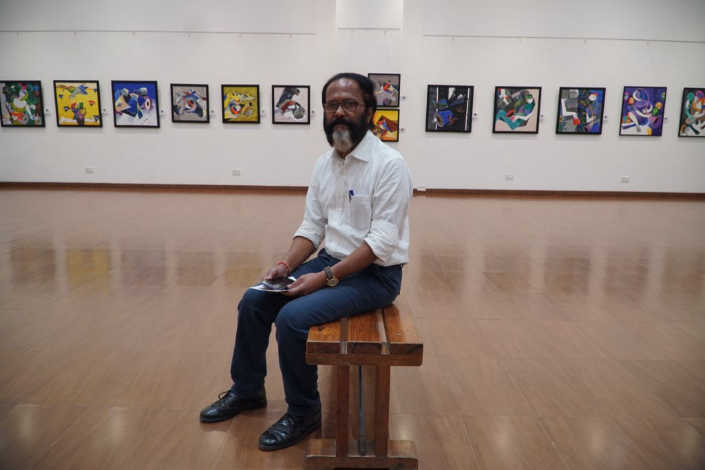 Artist Pradip Sarkar at Nehru Centre, Mumbai with his paintings in the background