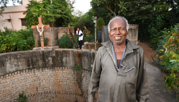 Octogenarian Simon Oraon Minj, aka Pani Baba, lives a simple life. His community-based water conservation initiative changed 51 villages. In this photo, he stands in front of the open well and a family member is drawing water manually