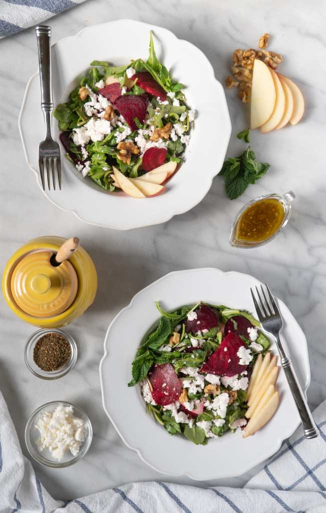 Roasted Beet Salad in bowls with forks, honey jar, and apple slices.