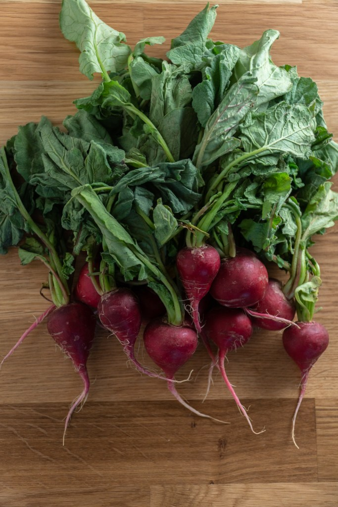 A bunch of radishes with leafy greens on a wooden cutting board