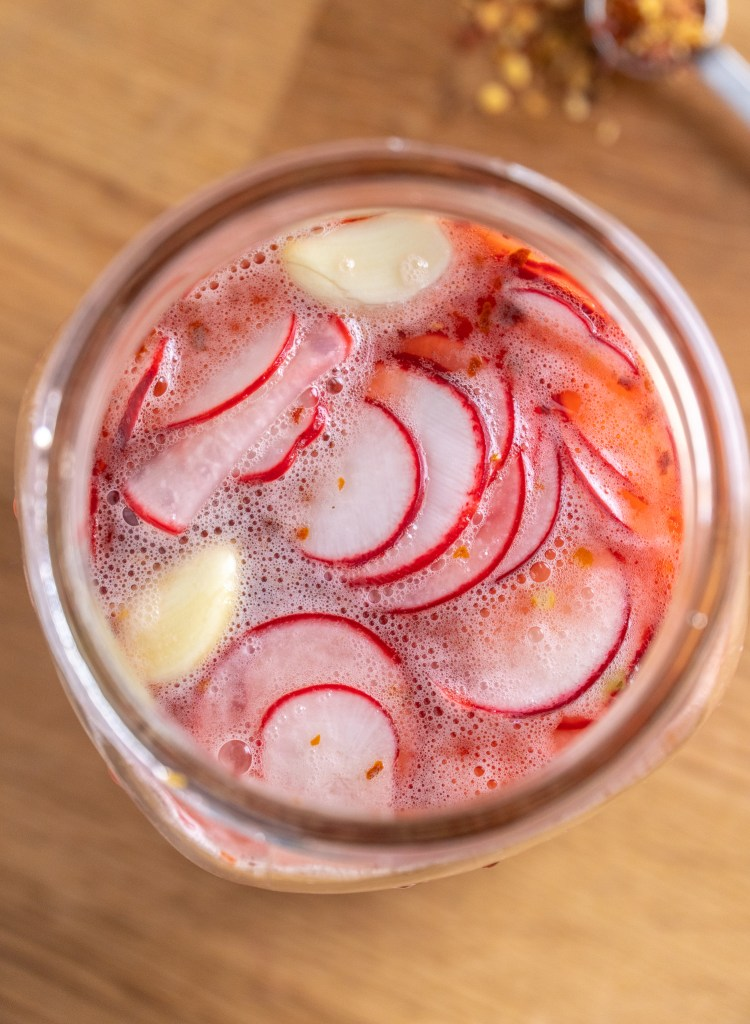 Looking down into a jar of thinly sliced quick pickled radishes with garlic cloves