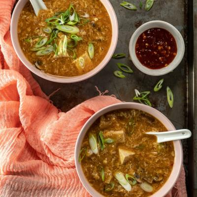 Bowls of warm Hot and Sour Soup sprinkled with green onions and served with a side of chili paste.