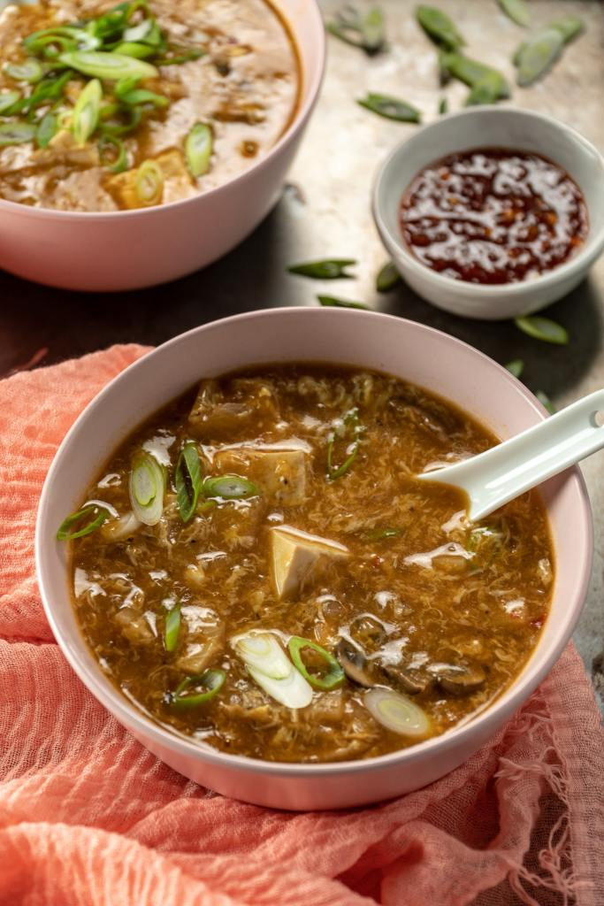 Bowl of hot and sour soup with a side of chili paste