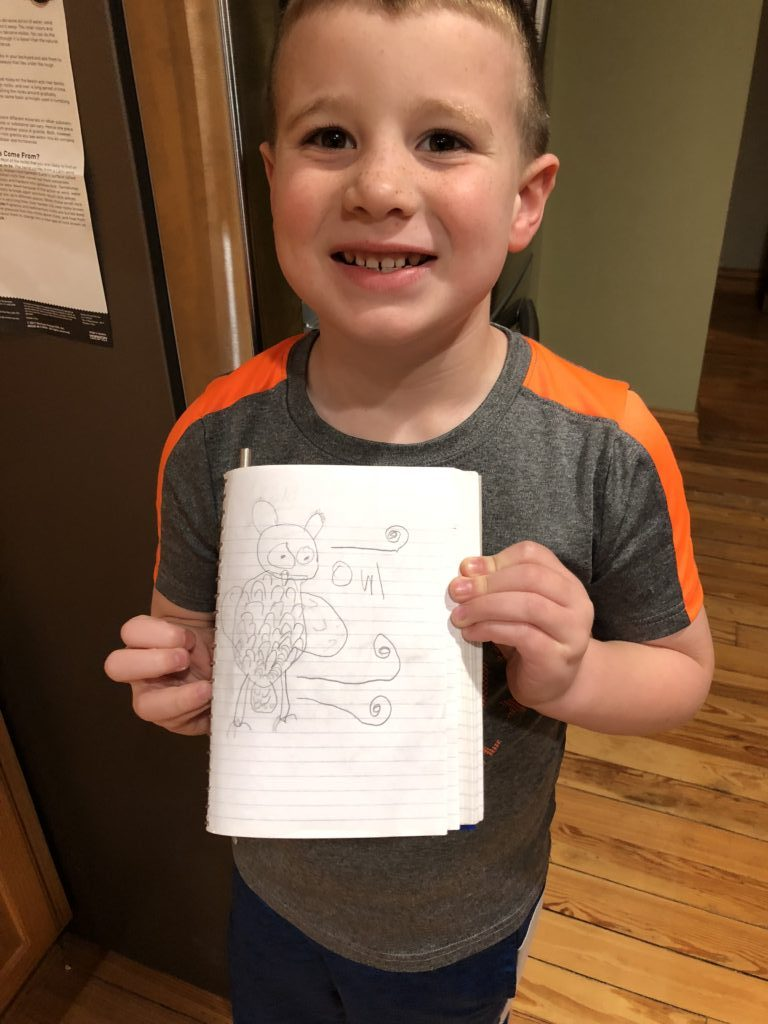 A young caucasian child holds a drawing of an owl.