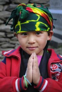 "Caption: Sangmo, a Nepalese girl, makes the classic greeting sign, namaste.  Her well-deserved nickname is ""Buta Maya"" which means ""sweet little thing."" Sangmo and her family came to the clinic where Ken Harvey volunteered in Nepal.  The wrap on her head, while in nontraditional colors, tells a bit of her heritage. Harvey will speak and show his photos of Nepal at the Nashua Public Library on January 7 at 7 p.m. Photo credit: Ken Harvey"