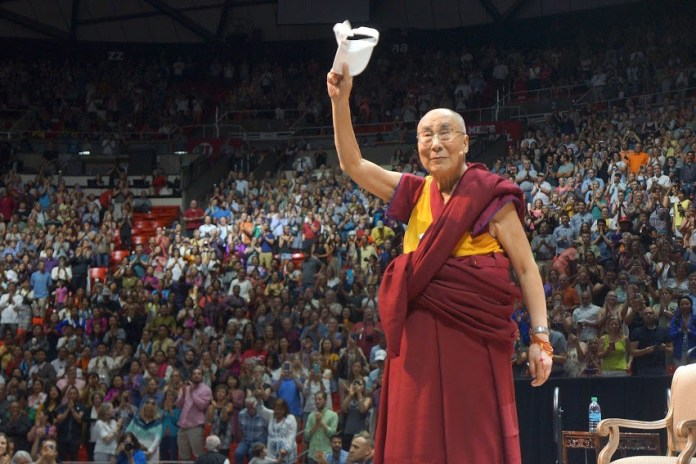"""His Holiness the Dalai Lama waving to the audience at the end of his talk on """"Compassion and Universal Responsibility"""" at the University of Utah's Huntsman Center in Salt Lake City, Utah on June 21, 2016. (Photo/Jeremy Russell/OHHDL)"""