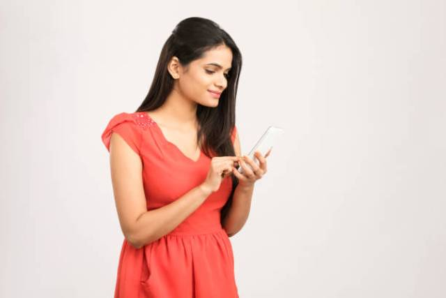 Pretty Young Woman Using Smart Phone On White
