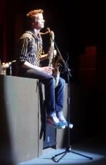 Derek Brown sitting on the stage.(photo Emilia Galvez, La Cochera Cultural)R.