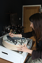 Sharyn Turner painting ravens onto a shamanic drum