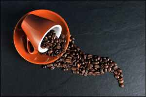 A red coffee cup is tipped on a red plate. Beans spill artfully off the plate and onto the table.
