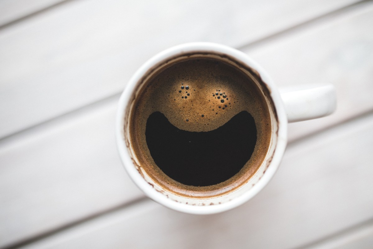 There is a cup of coffee on a table. It looks like the foam makes a crazy smiling face.