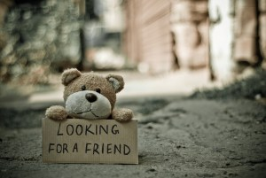"""A teddy bear sits on a sidewalk with a sign that says """"Looking for a friend"""""""