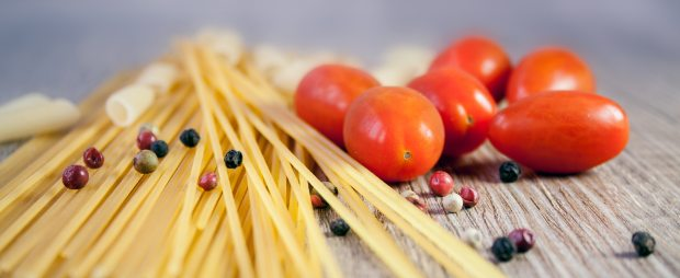 Some dry, uncooked pasta and cherry tomatoes sit on a cutting board.