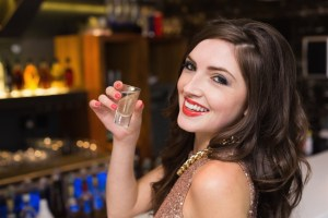 Pretty brunette drinking a shot at the bar