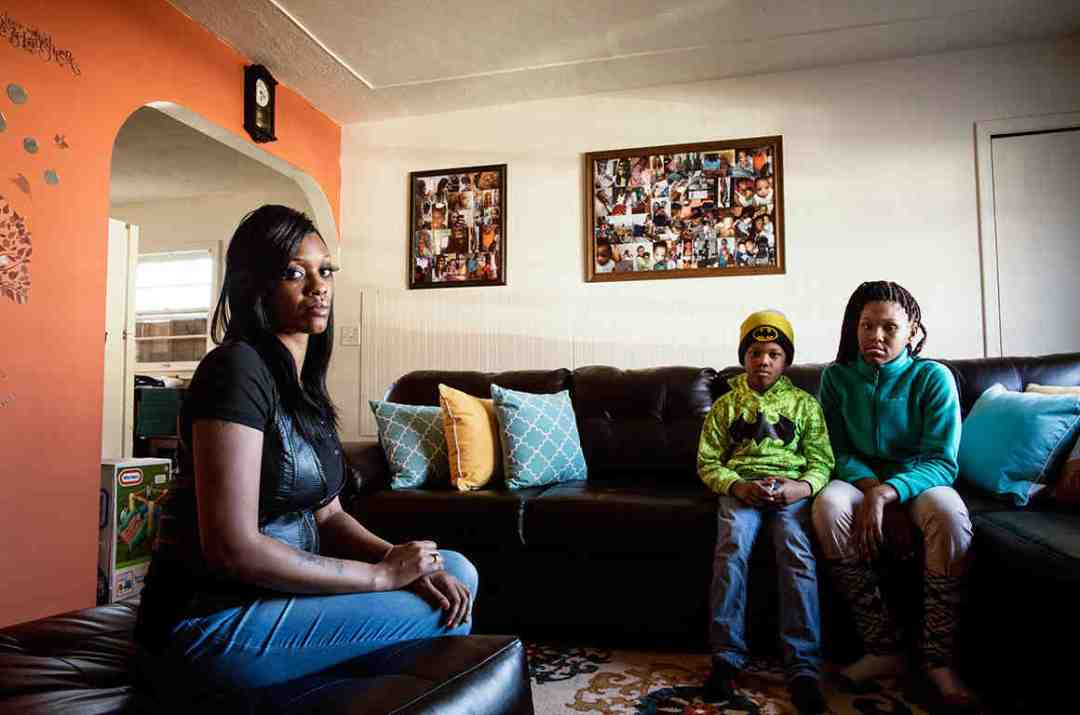 Tamesha Means sits in a living room with two other people, one of them a young boy. Family photos crowd two large frames on the wall above them.