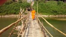 monaco che attraversa  un ponte sul mekong a Luang Prabang