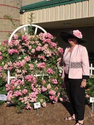 Peggy Martin from Louisiana standing by the rose that is named for her in the HCMGA rose garden!