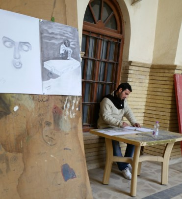An artist drawing at a corner in the Qisla