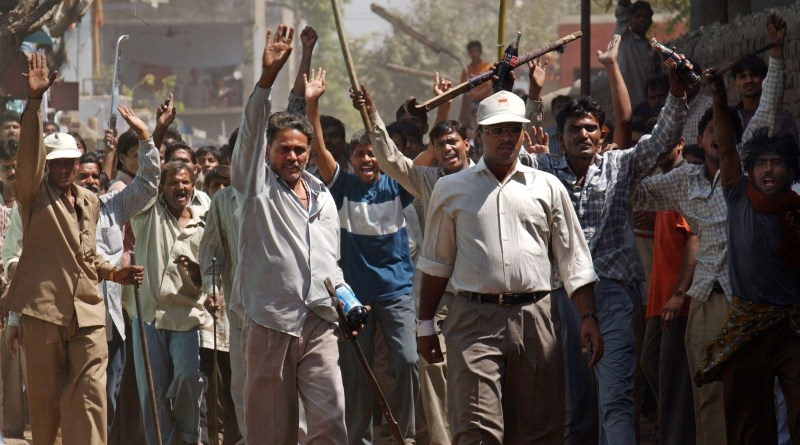 Hindu-Muslim Violence, riots, civil unrest. 401733 09: A mob of Hindus wielding swords and sticks back off after Indian Rapid Reaction Force officers stopped them from attacking a small group of Muslims March 1, 2002 in Ahmadabad, India, two days after a Muslim mob attacked a train, killing 58 people in the Indian state of Gujarat. Indian troops arrived in the riot-torn western state of Gujarat but were unable to quell the Hindu-Muslim violence that has claimed the lives of 251 people. (Photo by Ami Vitale/Getty Images)