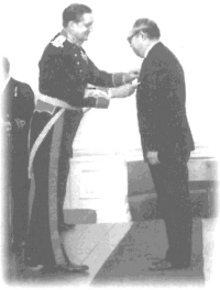 Peter Woo receiving his OBE medal from Governor MacLehose, 1975