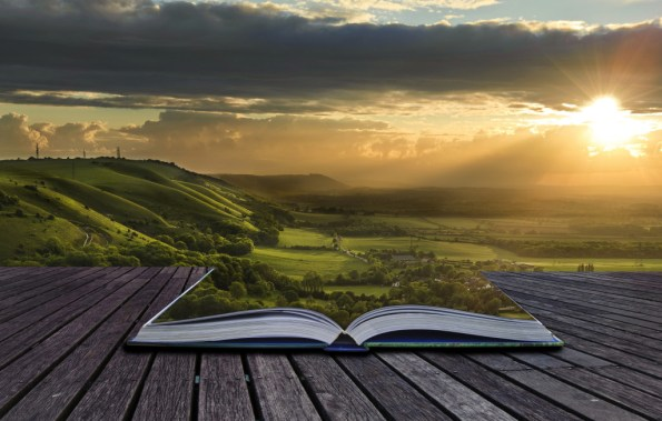 A country landscape emerges from an open book and fills the horizon.