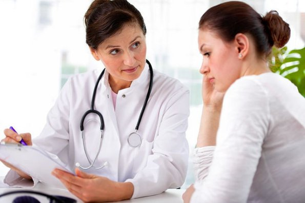 A doctor refers to a questionnaire on a chart while consulting with a female patient who exhibits some symptoms of depression.