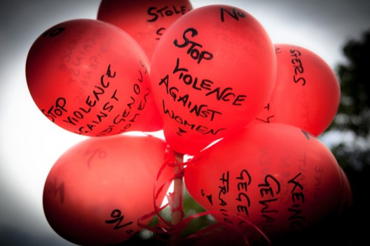 "Red balloons bearing the words ""stop violence against women."""